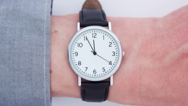 Close up of a man wearing a wrist watch Close up time-lapse of a wrist watch on a man`s wrist approaching 12 o' clock wristwatch stock videos & royalty-free footage
