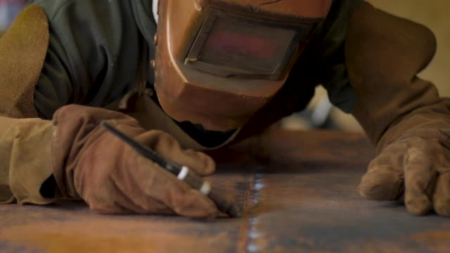 Close up of a man welding two pieces of copper together in slow motion Close up of a man welding two pieces of copper together in slow motion copper stock videos & royalty-free footage