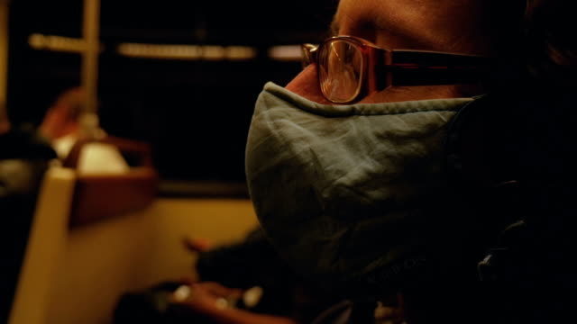 close up of a man with glasses wearing a respiratory mask on a subway - public health filmów i materiałów b-roll