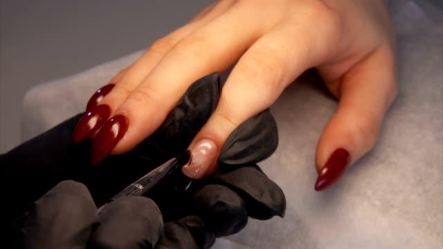 närbild av en manikyrister händer korrigera en nagelform med en gel - nagellack bildbanksvideor och videomaterial från bakom kulisserna
