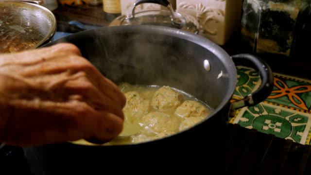 nahaufnahme der hand eines mannes rühren und kochen matzah kugelsuppe auf herd - kloß stock-videos und b-roll-filmmaterial