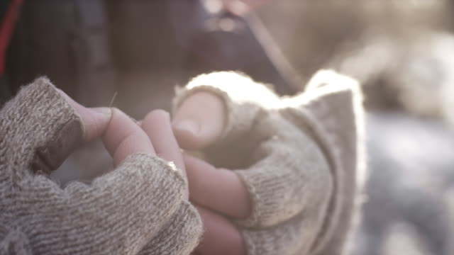Close up of a man's hands as he threads and ties his lure to his fishing line video