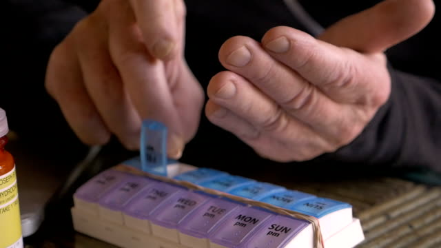 close up of a man's hands filling his daily pill planner with medication - prescrizione medica video stock e b–roll