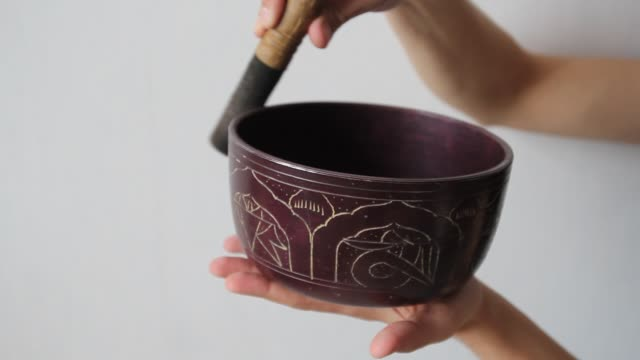 close up of a man's hands playing a tibetan singing bowl with a wooden stick against white wall