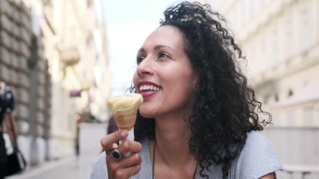 vídeos de stock, filmes e b-roll de feche acima de uma mulher latino-americano madura com o afro que come o gelado nas ruas de budapest - gelato