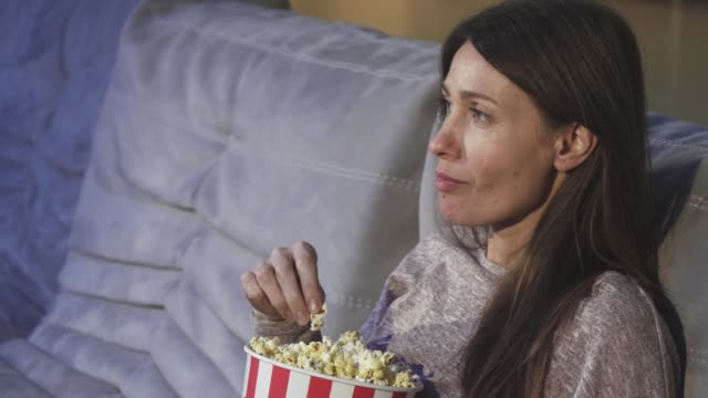 Close up of a mature woman eating popcorn smiling at the cinema video