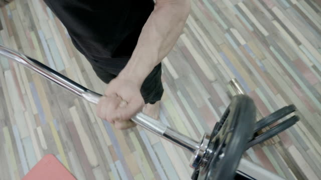 Close up of a muscle man working out his arms in a gym gym by lifting dumbbells video