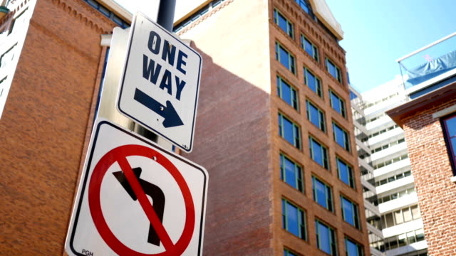 A close up of a one way road sign in downtown area video