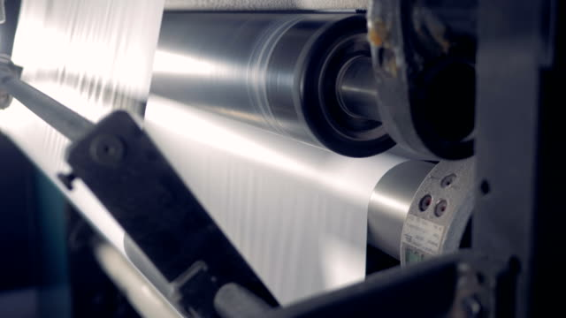 Close up of a paper rolling on a production line. Paper recycling factory equipment. video