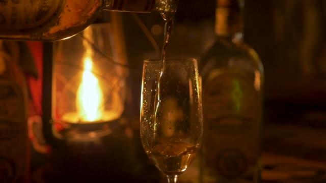bir kişi dökme tekila fener tarafından yaktı bir şampanya flüt yakın çekim - bar i̇çkili mekan stok videoları ve detay görüntü çekimi