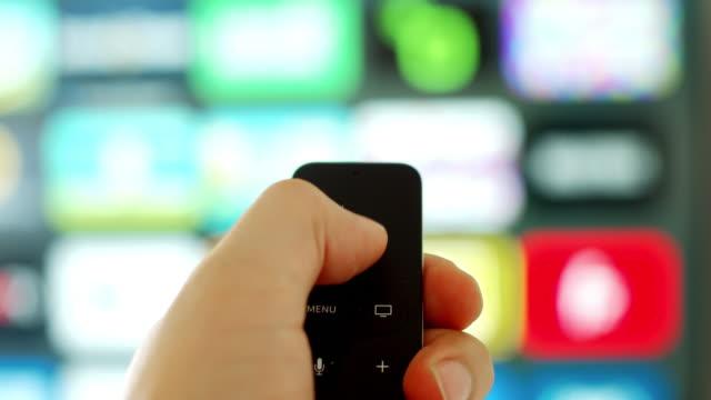 vídeos de stock, filmes e b-roll de feche acima da mão de uma pessoa segurando um reprodutor de mídia digital e controle remoto de microconsole com uma tela de televisão no fundo - live