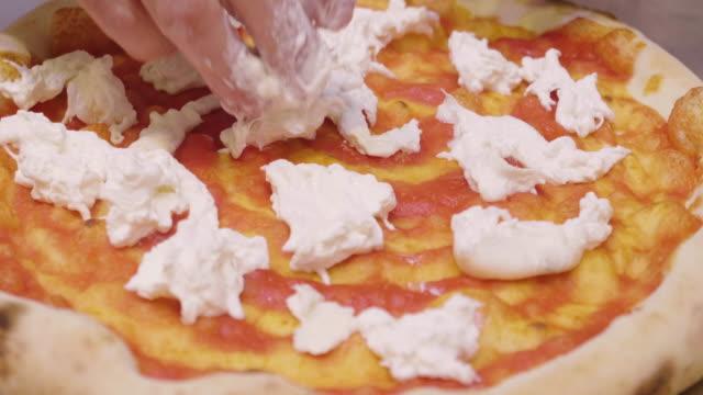 vídeos de stock, filmes e b-roll de feche acima das mãos de um cozinheiro chefe da pizza que enchem uma pizza com os ingredientes gastronômicos italianos da alta qualidade, como: presunto, vários queijos, tomates e vegetais frescos e bio - junk food