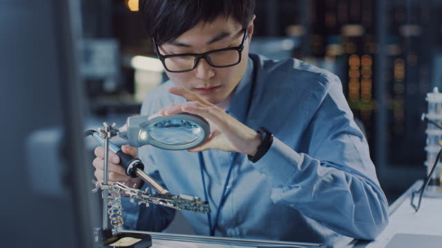close up of a professional japanese electronics development engineer in blue shirt soldering a circuit board in a high tech research laboratory with modern computer equipment. - apprendista video stock e b–roll