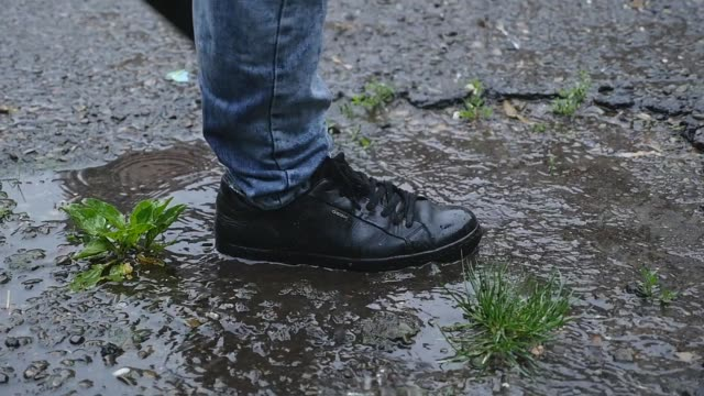 vídeos de stock e filmes b-roll de slow motion: close up of a puddle and a male in black shoes stepping into the puddle - poça