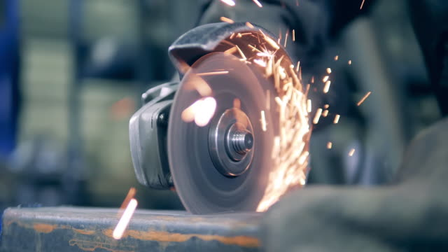 vídeos de stock e filmes b-roll de close up of a rotary saw cutting metal with sparks - moedor