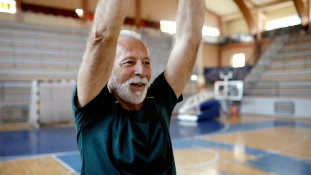 Close up of a senior man doing exercise at aerobic class