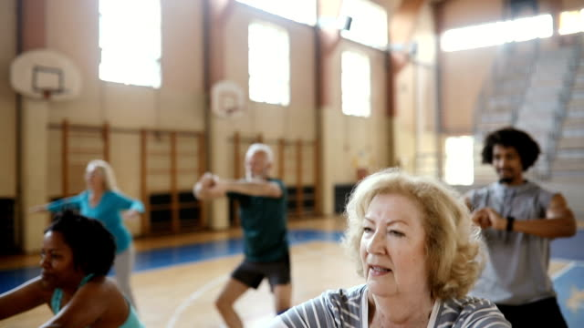 Close up of a senior woman doing exercise at aerobic class