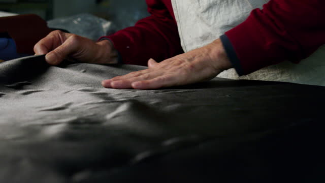 彼はイタリアの伝統を使用している靴工場で生地を働く靴メーカーのクローズアップ。 - 革点の映像素材/bロール