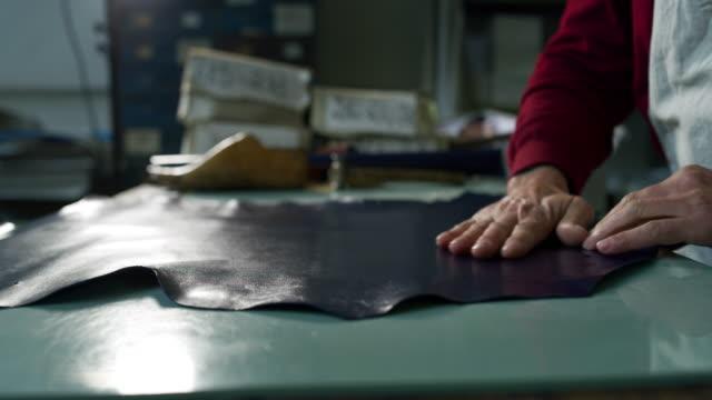 primo tempo di un calzolaio che lavora un tessuto in un calzaturificio che sta usando la tradizione italiana. - decorazione festiva video stock e b–roll