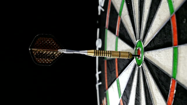 Close up of a single dart hitting the bull's eye on a dart board
