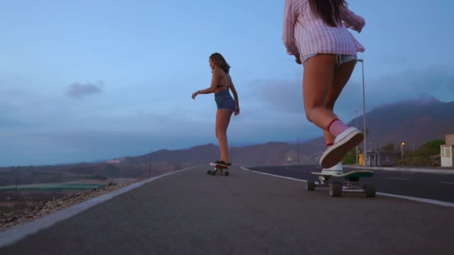 close - up of a skateboard and two girls who are riding on boards from a mountain on a background of rocks and sky. slow motion steadicam - retro fashion stock videos & royalty-free footage