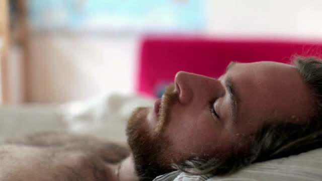 Close up of a sleeping man waking up video