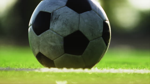 Close up of a soccer ball being kicked back into play Close up of a soccer ball being kicked back into play kicking stock videos & royalty-free footage