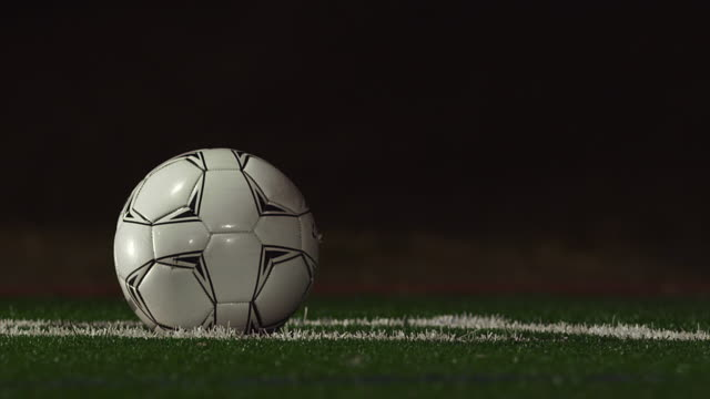 Close up of a soccer ball being kicked by a player in slow motion at night video