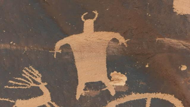 close up of a strange human like figure on newspaper rock in utah