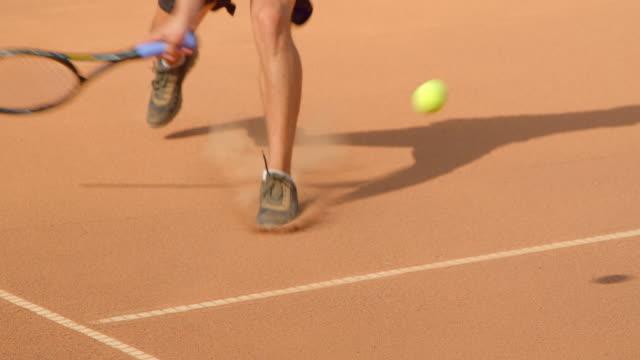 Nahaufnahme eines Tennisspielers, der einen Schuss auf einen Sandtennisplatz abgibt. – Video