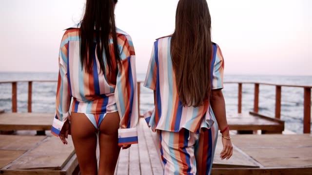 Zwei wunderschöne gebräunte Modelle laufen durch hölzerne Pier hautnah. Brünette langhaarige Fit Mädchen in ähnlichen farbigen Sommerkleidung. Ansicht der Rückseite – Video
