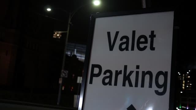 stockvideo's en b-roll-footage met close up van een teken van valet parking in centrum 's nachts - parkeren