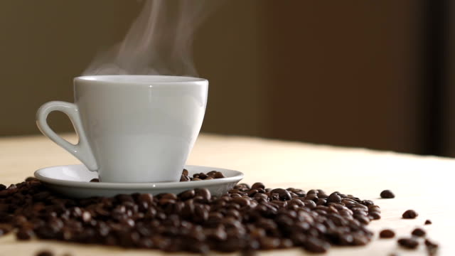 Close up of a white cup of evaporating coffee on table near roasted beans Close up of a white cup of evaporating coffee on the table near the roasted beans. Full HD coffee cup stock videos & royalty-free footage