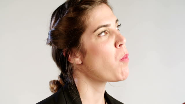 close up of a woman eating an apple on a white studio background video