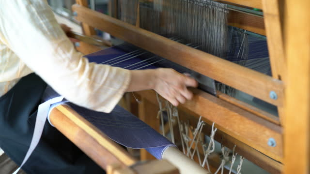 Close up of a woman hand weaving fabric, passing the shuttle back and forth video