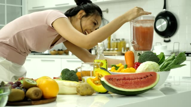 Close up of a woman making fresh juice from vegetables and fruits in kitchen at home.