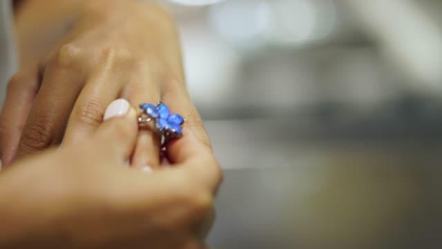 stockvideo's en b-roll-footage met close up van een vrouw probeert op een ring in een juwelier - ring juweel