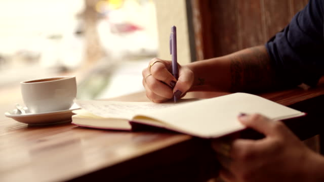 Close up of a Woman Writing Journal in Coffee Shop