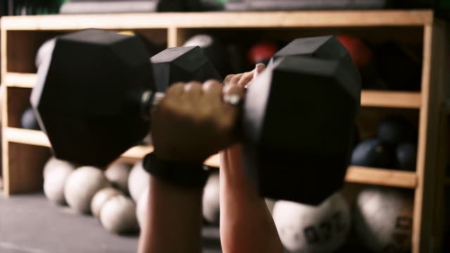 Close up of a woman's hands as she does a dumbbell bench press in a small gym video