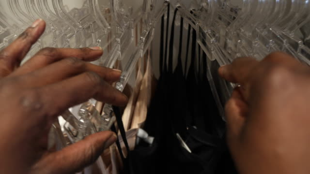 Close up of a woman's hands looking through clothes rack - video