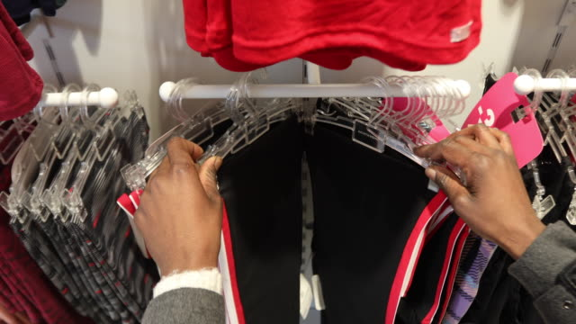 Close up of a woman's hands looking through clothes rack
