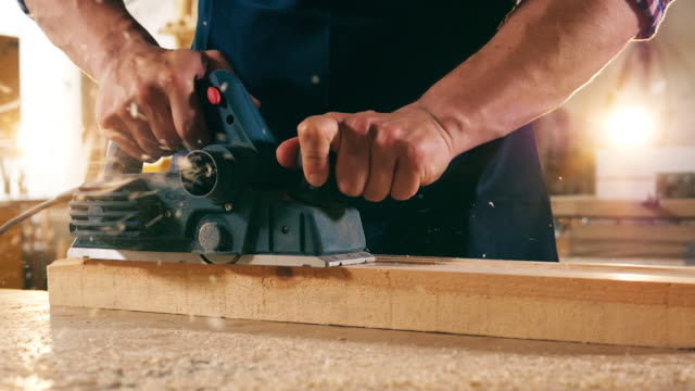 Close up of a wooden block getting sawn in slow motion