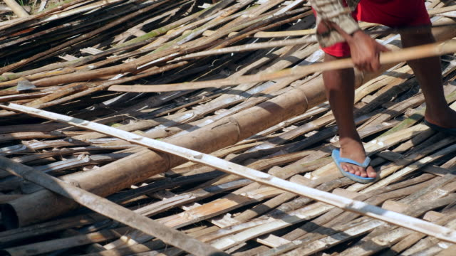 close up of a worker working with bamboo and weaving strips to make floors