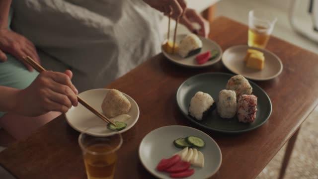 自宅で食事を楽しむ若いカップルのクローズアップ - 居間点の映像素材/bロール