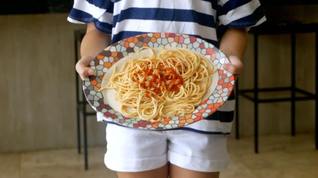 vidéos et rushes de fermez-vous vers le haut d'une jeune fille renversant une plaque de spaghetti sur l'étage - spaghetti renversé