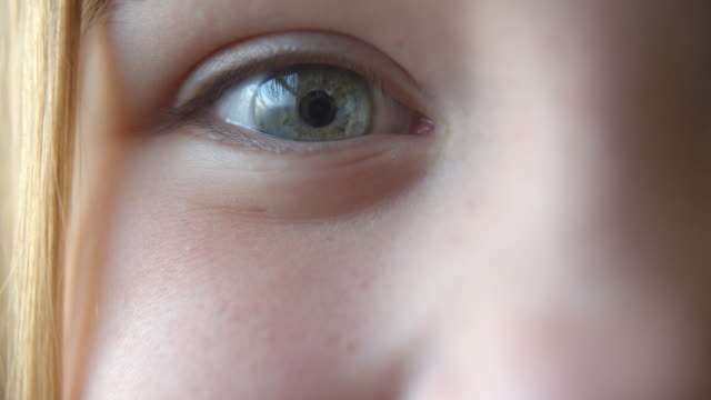 Close up of a young girl's eye as she changes expression Close up of a young girl's eye as she changes expression one girl only stock videos & royalty-free footage