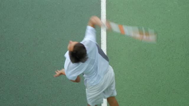 Eine Nahaufnahme eines jungen Mannes, der Tennis spielt, dient in Zeitlupe. – Video