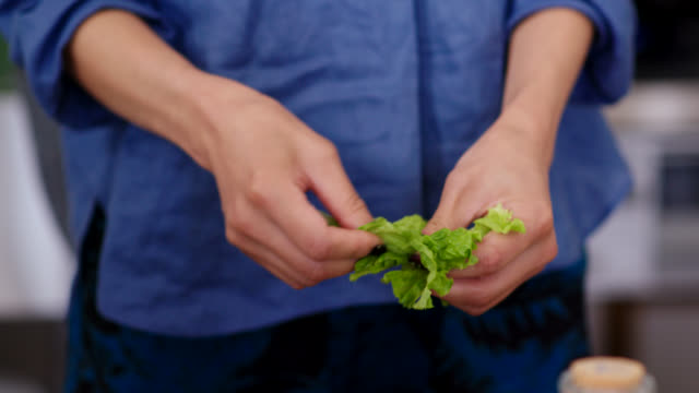 close up of a young woman tearing lettuce for a salad