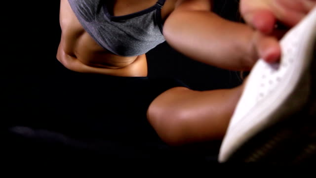 Close up of a young woman with sports body stretching against black background video