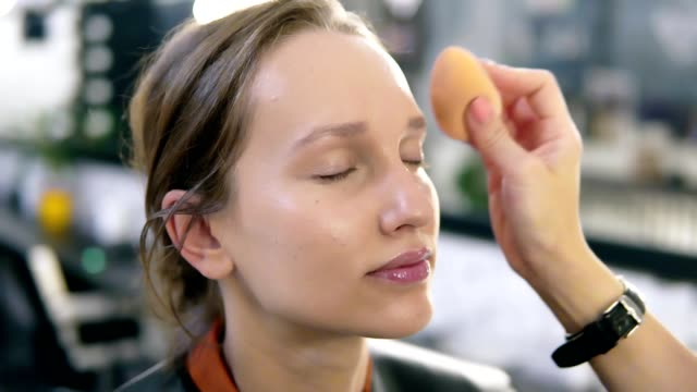 Close up of a young woman's face and artist hand putting on the tone with a sponge. Natural beauty. Studio Close up of a young woman's face and artist hand putting on the tone with a sponge. Natural beauty. Studio. foundation make up stock videos & royalty-free footage
